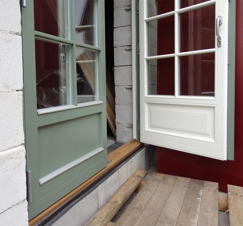 Grön fönsterdörr, vitmålad insida. Spröjs och isolerad fyllning