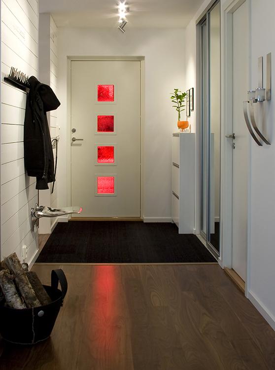 Denna Nagano-dörr har kunden valt att göra vit på insidan. Ett praktiskt val för att matcha insidan av hallen. De röda glasen är väldigt läckra och släpper även in ljus.