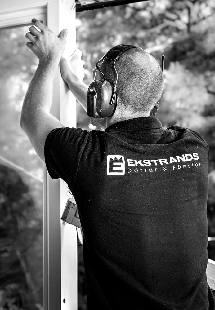 En av Ekstrands montörer jobbar med ett fönster vid installation.